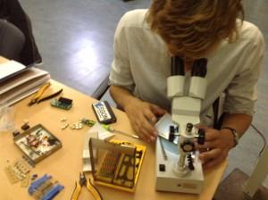 Wouter bekijkt een printplaat onder de microscoop.